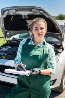 壊れた車についていくつかのメモを作る女性整備士