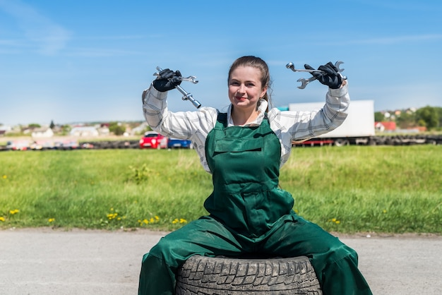 Woman mechanic posing with spanners and tyres