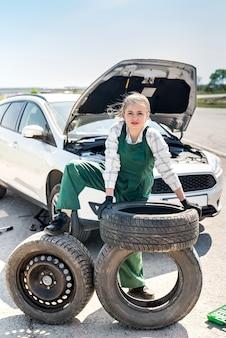 예비 바퀴와 타이어와 함께 포즈를 취하는 여자 정비사