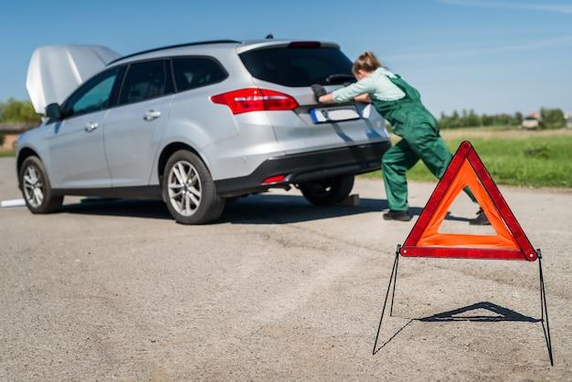 Woman mechanic pushing broken car on roadside