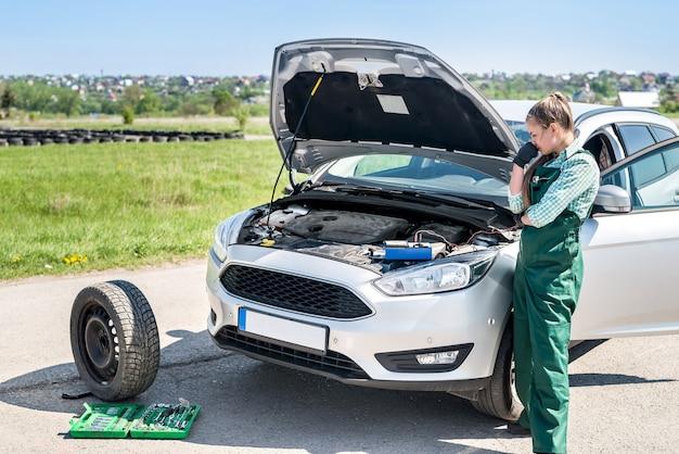 車のエンジンの問題を検索する女性整備士