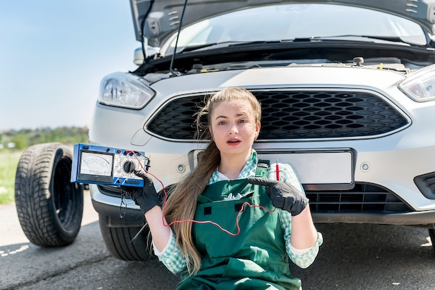 The woman mechanic sits near the broken car with tester