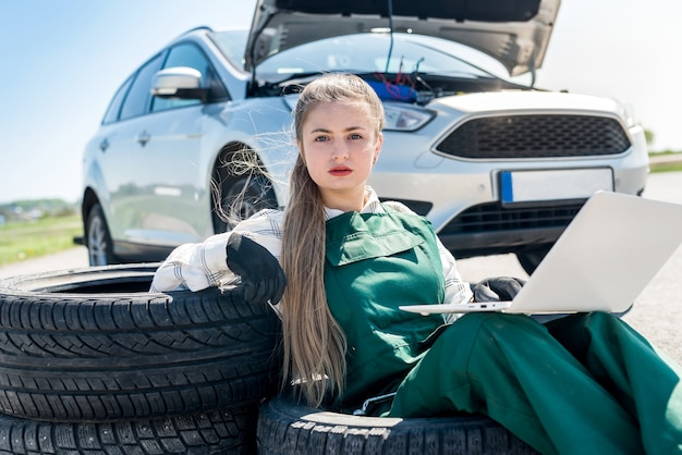 Woman mechanic with broken car and laptop