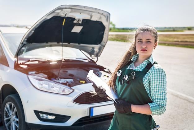 壊れた車の近くに立っているクリップボードを持つ女性整備士