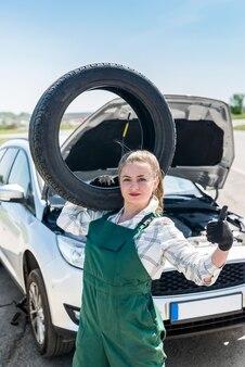어깨와 깨진 된 자동차에 타이어와 여자 정비공