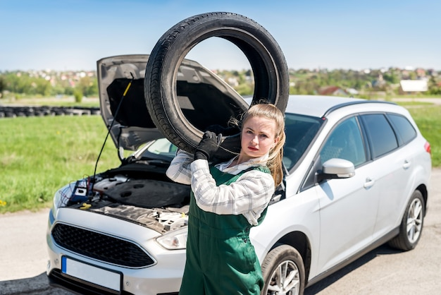 Woman mechanic with tyre on shoulder and broken car