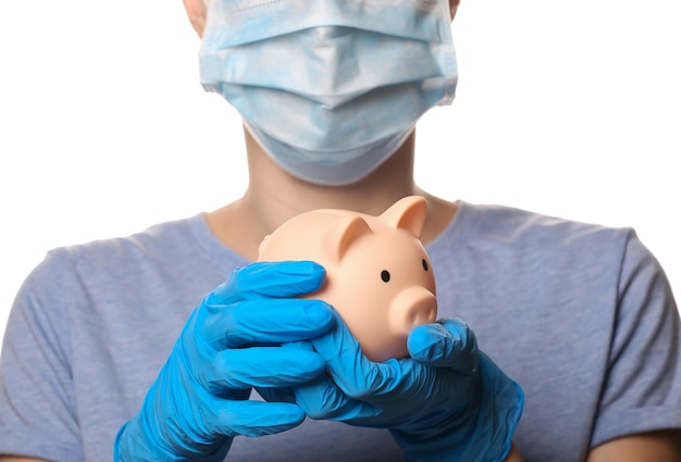 Woman in media mask and gloves holds piggy bank isolated on white