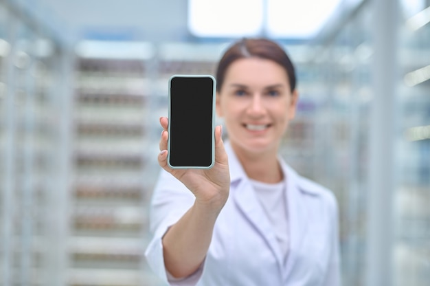 Woman in medical gown showing smartphone screen