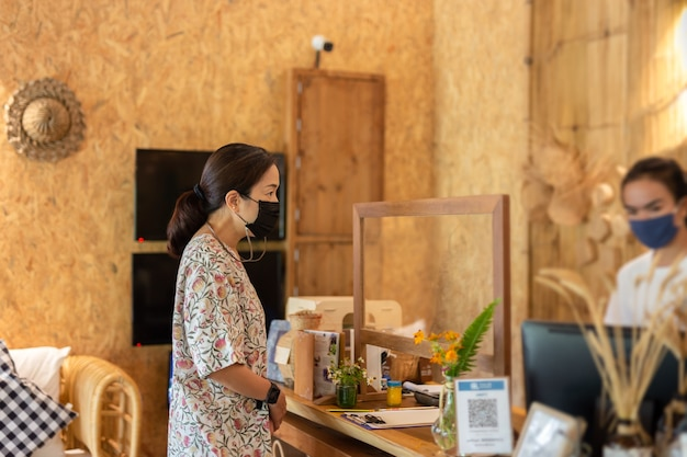 Woman in medical mask checking in at hotel reception