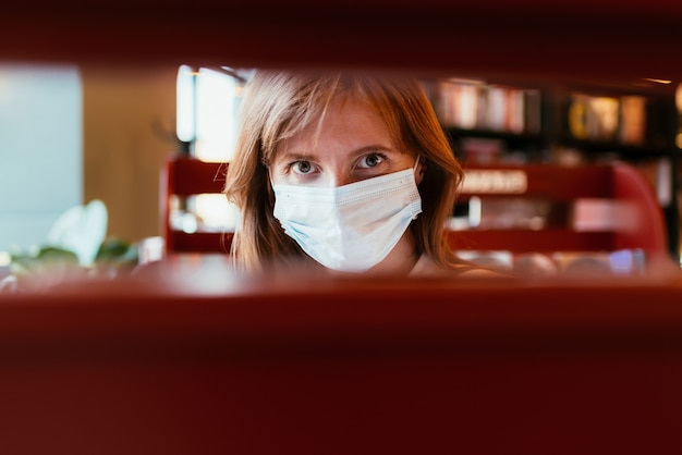 Woman in a medical mask chooses a book in a bookstore