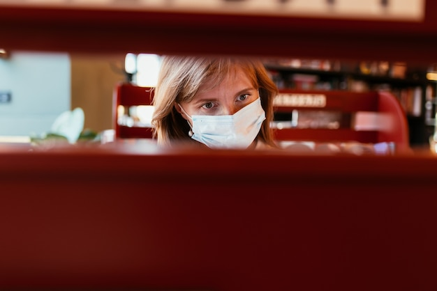 Woman in a medical mask chooses a book in the library