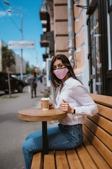 Woman in a medical mask drinks coffee on the street