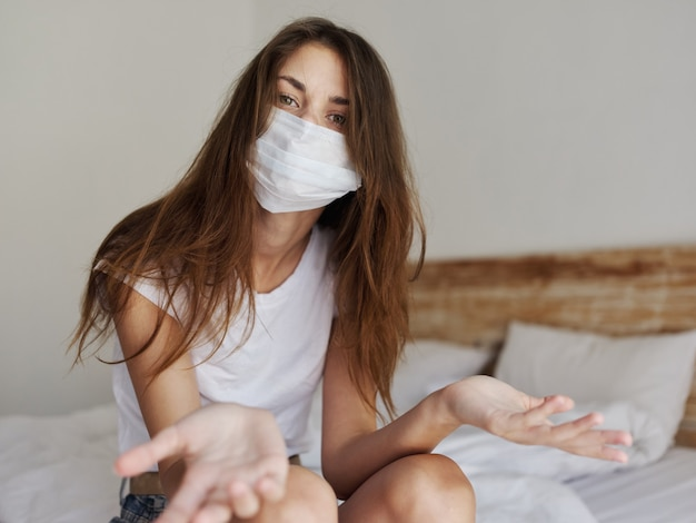 Woman in medical mask gesturing with her hands and sitting on the bed pandemic quarantine