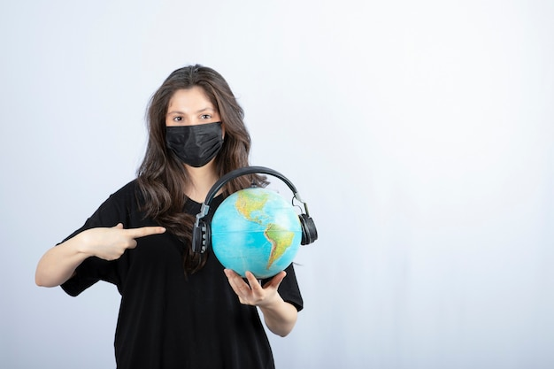 Woman in medical mask holding and pointing to globe on white table.