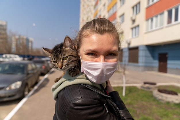 Woman in a medical mask is walking with a cat along the street near the house