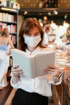 Woman in a medical mask in the library holding a book in her hands