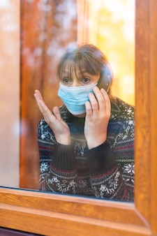 Woman in medical mask looking through window with hope