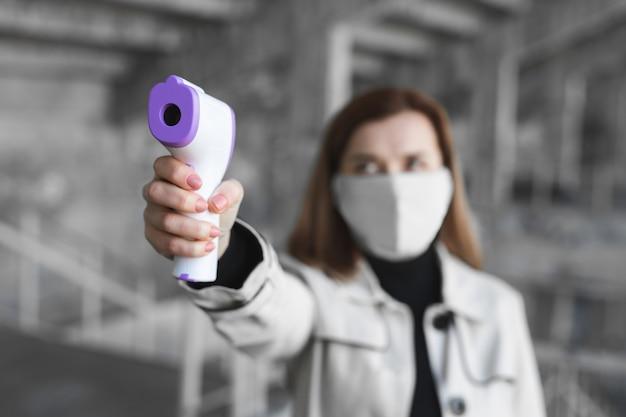 Woman in medical mask measures body temperature