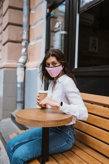 La donna in una maschera medica per prevenire le infezioni virali beve caffè per strada