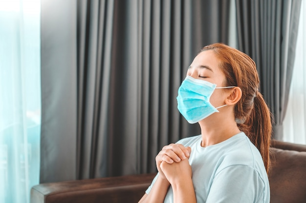 Woman in medical mask praying in the morning