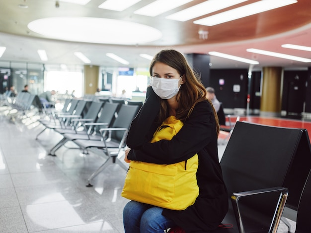 Woman in medical mask with luggage airport waiting flight delay