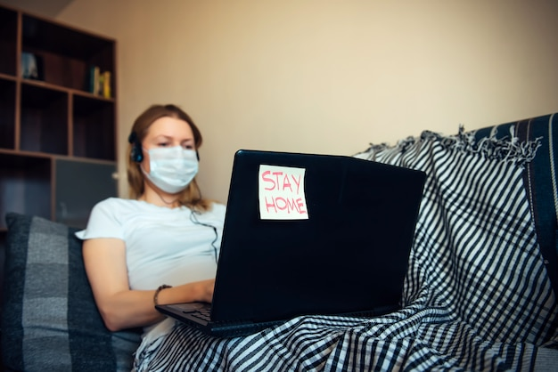Woman in medical mask working on laptop online from home. stay at home during a virus pandemic. quarantine, self-isolation, disease prevention concept. sticker with text
