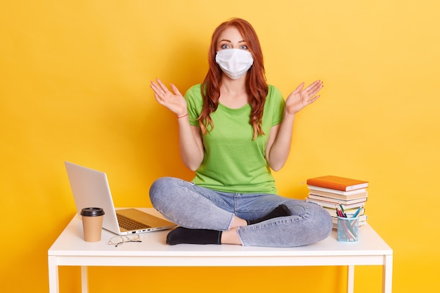 Woman in medical mask and , young girl dressed in green t shirt and jeans sitting on table with crossed legs