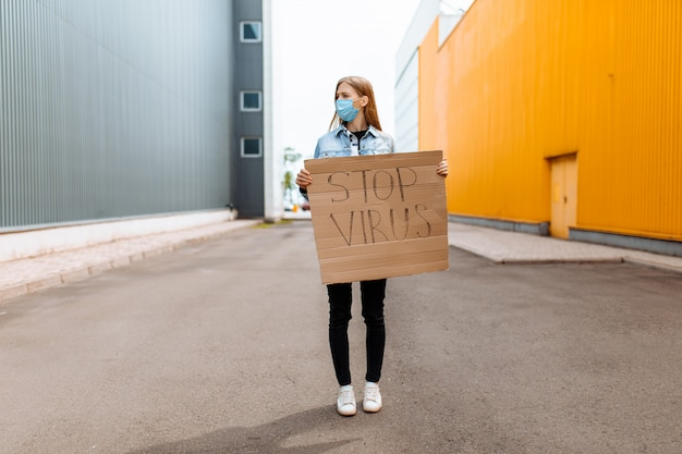 Woman in a medical protective mask holds a cardboard placard with the words stop the virus, on a street in the city