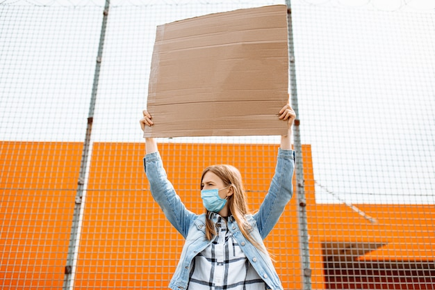 Woman in a medical protective mask holds an empty cardboard poster for a copy of the space, standing on a city street against a yellow wall