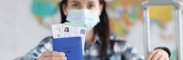 Woman in medical protective mask and suitcase shows her passport holds passport immunity from corona...