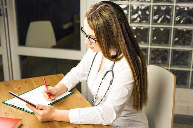 Женщина-врач держит банку с таблетками и выписывает рецепт пациенту за рабочим столом