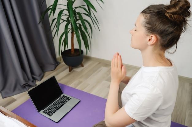 여자는 나마스테 손을 노트북으로 온라인 수업 자습서를 보면서 명상합니다.