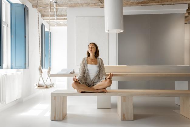 Женщина медитирует в современном доме
