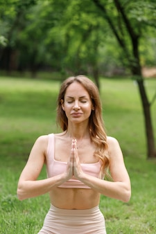 Woman meditates in city park on green yoga background