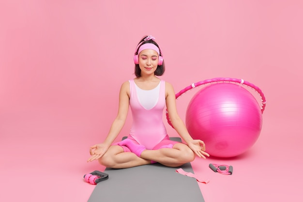 Woman meditates on fitness mat practices yoga sits crossed legs listens relaxing music via stereo headphones dressed in sportsclothes trains with swiss ball hula hoop sport equipment
