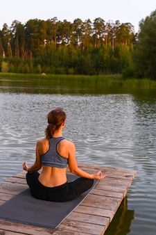 A woman meditates in nature by the lake. the concept of realizing the meaning of life.