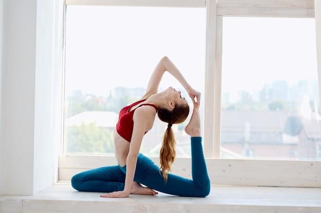 女性は窓の近くのトレーニング運動の調和を瞑想します