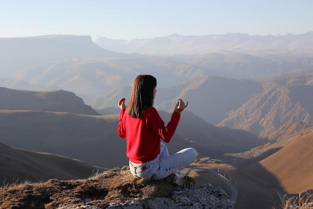 Женщина медитирует на горе