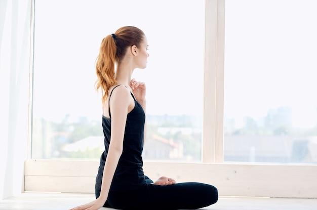 女性は窓のトレーニング運動の近くの窓辺で瞑想します