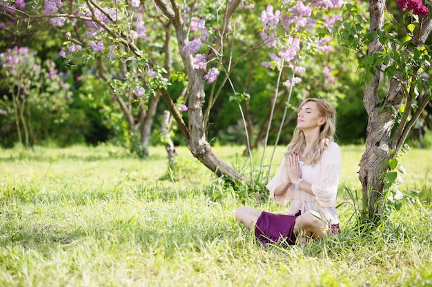 Женщина медитирует под кустом