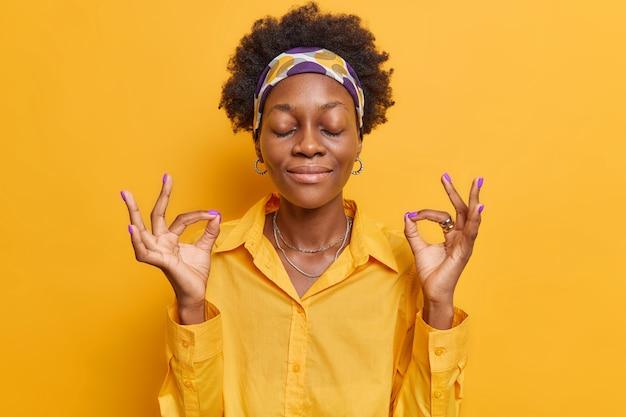 Женщина медитирует с закрытыми глазами, занимается йогой, держит руки в порядке, носит повседневную рубашку, позирует на ярко-желтом.