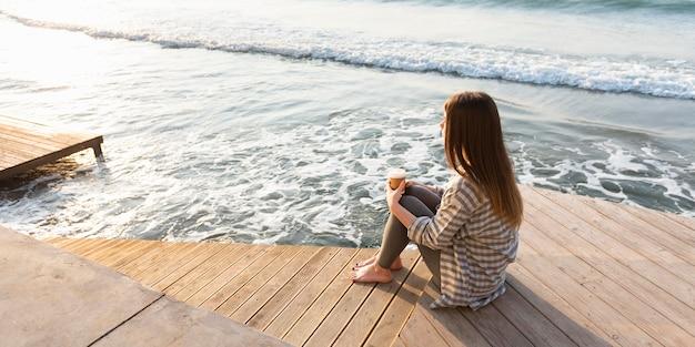 Женщина медитирует и смотрит на море