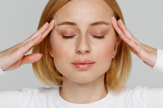 Женщина медитирует и массирует виски, закрывает глаза, снимает эмоциональное напряжение и нервное напряжение, изнуренная от переутомления Premium Фотографии