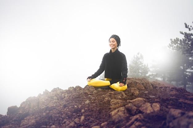 Женщина медитирует и практикует йогу на вершине горы