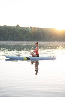 Женщина медитирует и практикует йогу во время восхода солнца в лопаточной доске