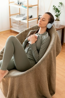 Женщина медитирует дома на стуле