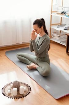 Женщина медитирует дома на коврике