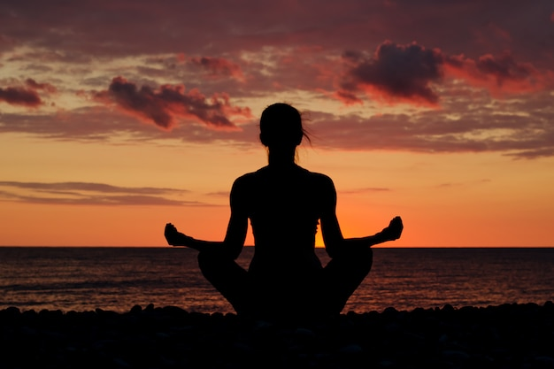 Woman meditating on the beach in lotus position. silhouette, sunset