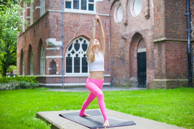 Woman  meditating and doing yoga asana exercisers in city street
