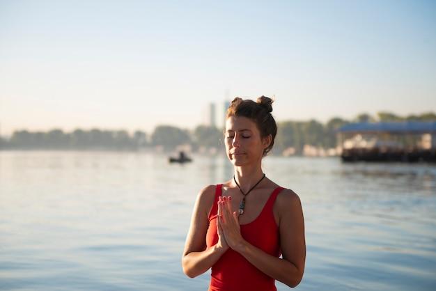 Женщина медитирует во время восхода солнца на берегу моря